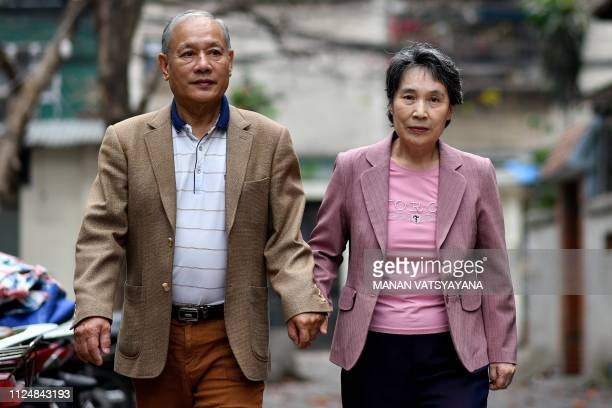 Vietnamese man Pham Ngoc Canh and his North Korean wife Ri Yong Hui walk holding hands in an alley outside their house in Hanoi on February 13 2019 A...