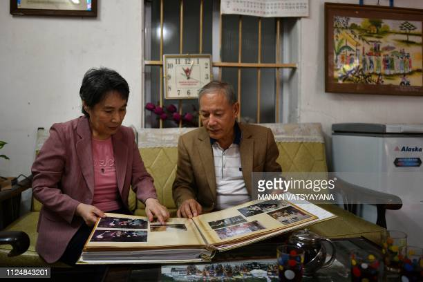 Vietnamese man Pham Ngoc Canh and his North Korean wife Ri Yong Hui look at their wedding album at their house in Hanoi on February 13 2019 A...