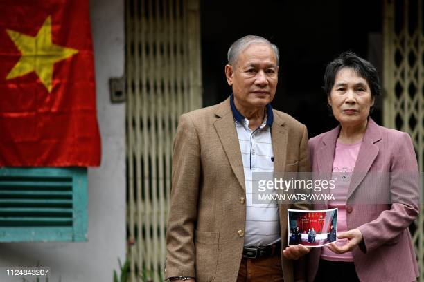 TOPSHOT Vietnamese man Pham Ngoc Canh and his North Korean wife Ri Yong Hui pose together holding their wedding photograph outside their house in...