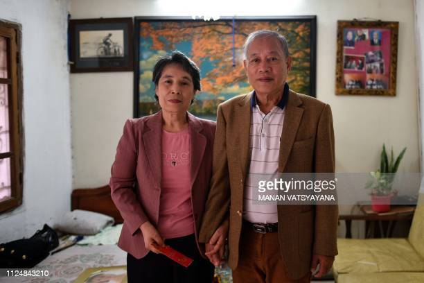 Vietnamese man Pham Ngoc Canh and his North Korean wife Ri Yong Hui pose inside their house in Hanoi on February 13 2019 A handkerchief illicit...