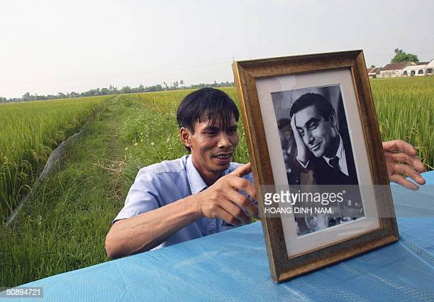 Vietnamese man places a portrait of the world famous war photographer Robert Capa of the US on a table prior to a memorial service 25 May 2004 the...