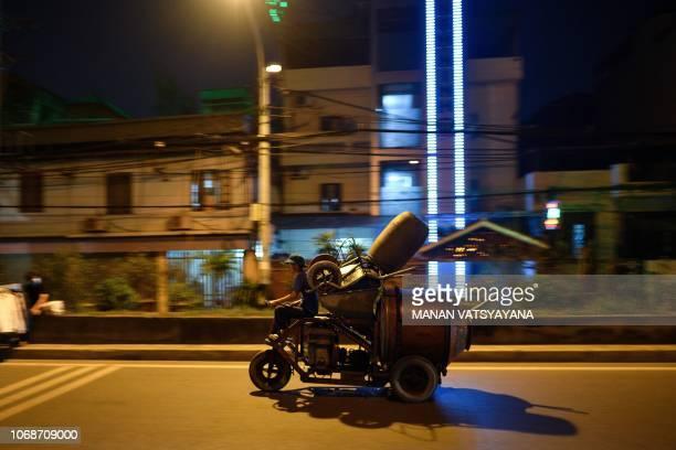 A Vietnamese man rides his makeshift concretemixer on a street in Hanoi on December 5 2018