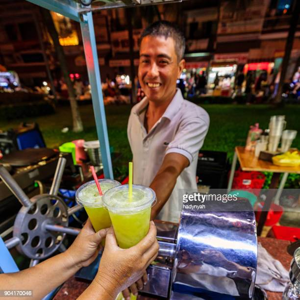 vietnamese man selling sugar cane juice on night market, mekong river delta, vietnam - can tho province stock pictures, royalty-free photos & images
