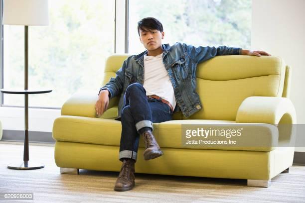 Vietnamese man sitting on sofa