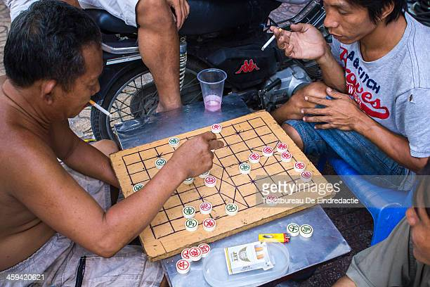 Vietnamese men, smoking and arguing over a game of XiangQi, or Chinese chess, on the streets of Hanoi, Vietnam.