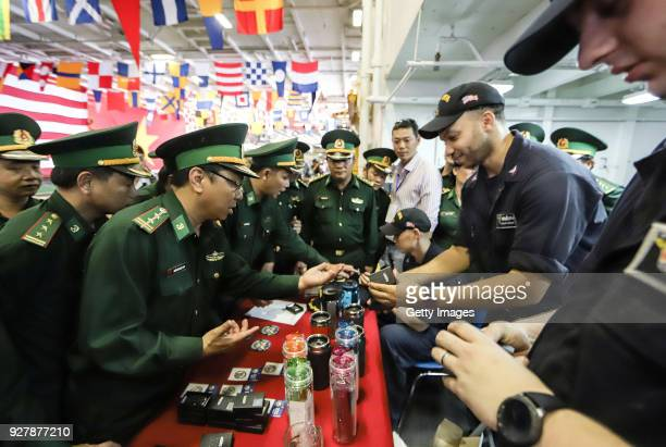 Vietnamese military offers purchase souvenirs during a tour onboard the USS Carl Vinson at Tien Sa Port on March 5 2018 in Danang Vietnam A United...