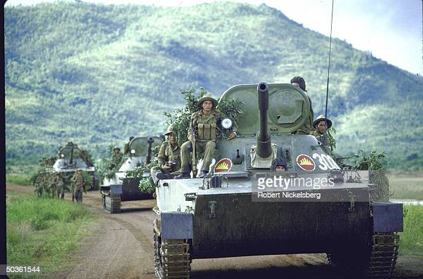 Vietnamese military personnel riding on tanks while on maneuvers in Cambodia