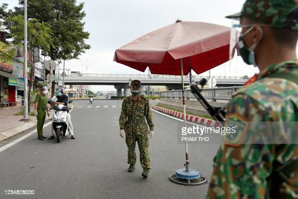 Vietnamese military personnel stand guard at a checkpoint in Ho Chi Minh City on August 23 after the government imposed a stricter lockdown until...