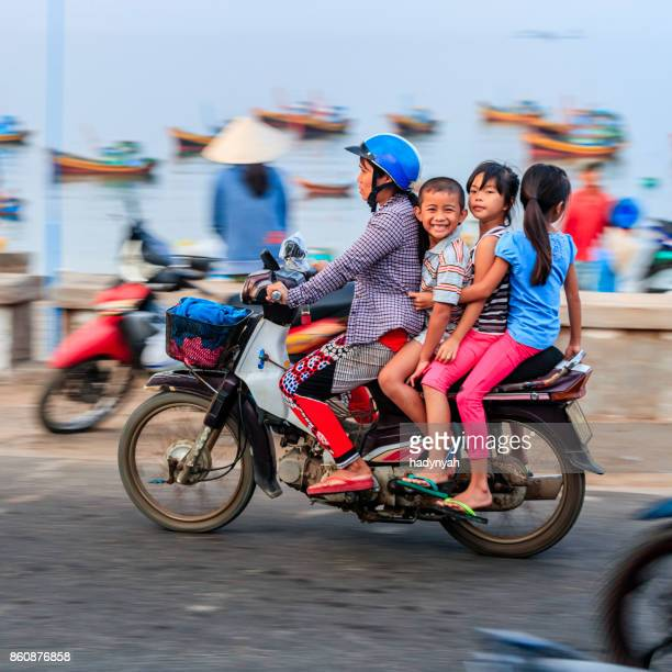 vietnamese mother with children riding a motorbike, south vietnam - traditionally vietnamese stock pictures, royalty-free photos & images