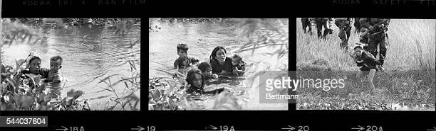 Vietnamese mothers and their children wade across a river fleeing a bombing raid on Qui Nhon by United States aircraft The raid was organized to...
