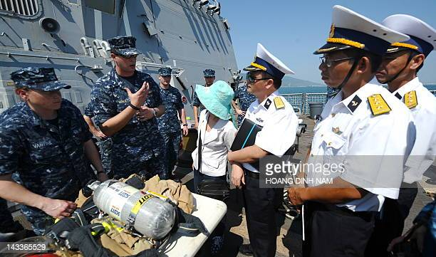 Vietnamese navy's officers look at a US sailor demonstrating the fire control skills aboard the guided missile destroyer USS Chafee during a disaster...