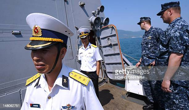 Vietnamese navy's officers walk aboard the guided missile destroyer USS Chafee during a disaster control training with US sailors at Tien Sa port in...