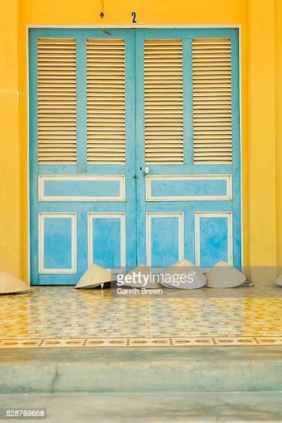 Vietnamese 'Non La' Hats Beneath Shuttered Blue and Yellow Door