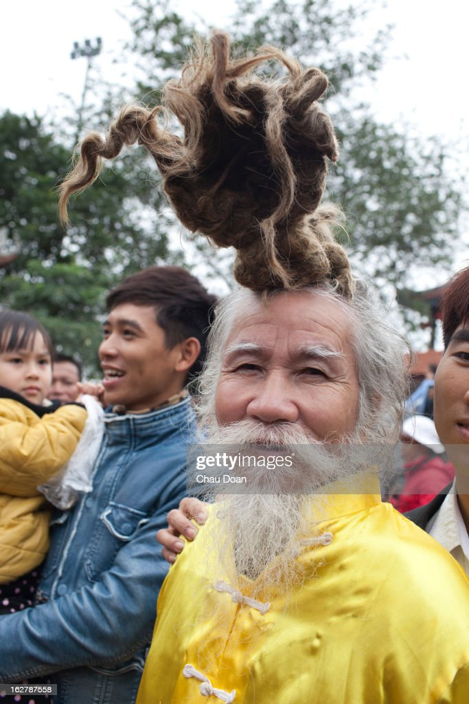 Vietnamese people pose for photo with an old man who has an unique hairstyle at the Lim festival. The Lim festival takes place at the 13th day of the first lunar month in Lim village, about 18 kilometers from Hanoi. This is one of the most well-known festivals in Vietnam when folk songs called Quan Ho are performed. The legend says that a woman named Ba Mu, who attained enlightenment after becoming a Buddhist monk at the Lim pagoda, had ended a drought in the village on the request of the villagers. Henceforth the people of the village worshipped her as their protector and took the date of her enlightenment as the date of the festival in Vietnam. Quan Ho is the dialog performance between male singers and female singers. The singers have to be quick witted and have strong grasp of traditional tunes, history and meaning of the songs..