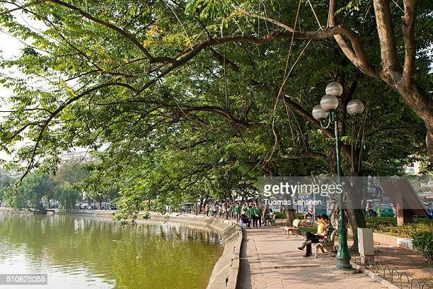 Vietnamese people strolling and relaxing under the shade of big trees at a park next to Hoan Kiem Lake in Hanoi, Vietnam. Hoan Kiem Lake is located...