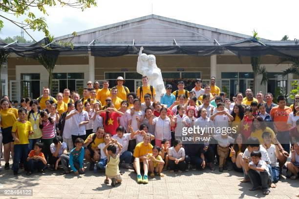 Vietnamese people suffering the affects of Agent Orange pose with crewmembers of the USS Carl Vinson at a centre for victims of the wartime defoliant...