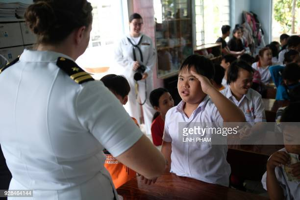 A Vietnamese person suffering the affects of Agent Orange salutes a US Navy sailor during a visit by the crew of USS Carl Vinson in Danang on March 7...