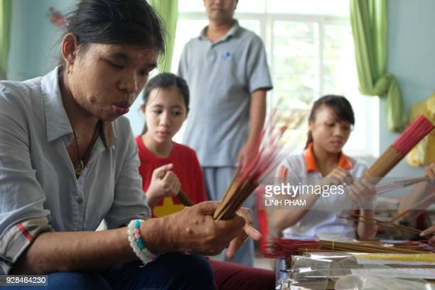 A Vietnamese person suffering the affects of Agent Orange wraps incense sticks at a centre for victims of the wartime defoliant during a visit by the...