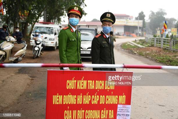 Vietnamese police wearing protective facemasks amid concerns of the COVID-19 coronavirus outbreak stand guard at a checkpoint in Son Loi commune in...