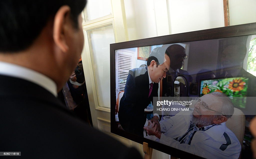 Vietnamese President Tran Dai Quang (L) looks at a photograph showing his last week meeting with Fidel Castro as he pays tribute to the late Cuban leader at the Cuban embassy in Hanoi on November 28, 2016. Communist heavyweights China and Vietnam were swift to lament the death of Fidel Castro, with Hanoi's state media leading tributes to the loss of a 'great friend and comrade'. / AFP / HOANG