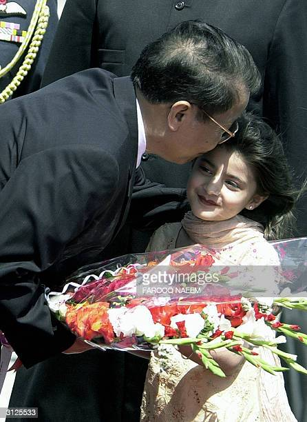 Vietnamese President Tran Duc Luong kisses a young Pakistani girl after she presented him with a bouquet of flowers upon his arrival at Chaklala Air...