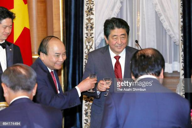 Vietnamese Prime Minister Nguyen Xuan Phuc and Japanese Prime Minister Shinzo Abe toast glasses during a dinner at Abe's official residence on June 6...
