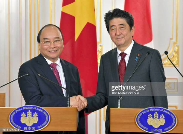 Vietnamese Prime Minister Nguyen Xuan Phuc and Japanese Prime Minister Shinzo Abe shake hands at a joint press conference following their meeting at...