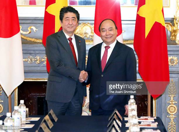 Vietnamese Prime Minister Nguyen Xuan Phuc and Prime Minister Shinzo Abe shake hands piror to their meeting at the Akasaka State Guest House on June...