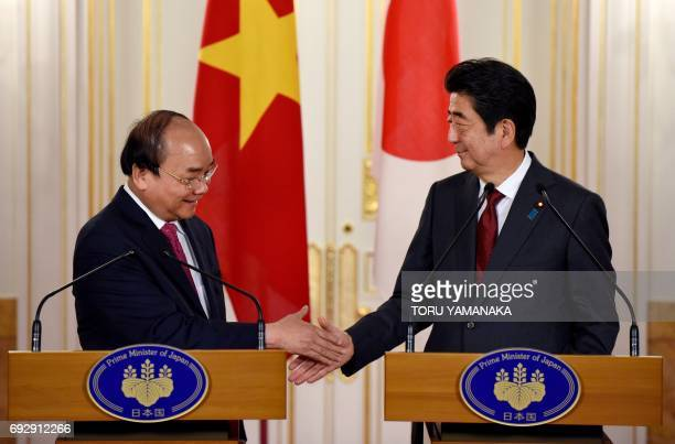 Vietnamese Prime Minister Nguyen Xuan Phuc shakes hands with his Japanese counterpart Shinzo Abe during a press briefing after their meeting in the...