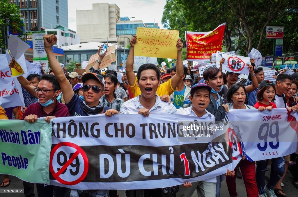 Vietnamese protesters shout slogans against a proposal to grant companies lengthy land leases during a demonstration in Ho Chi Minh City on June 10, 2018. - The draft law at the centre of the furore would allow 99-year concessions in planned special economic zones, which some view as sweetheart deals for foreign and specifically Chinese firms.