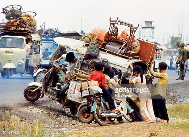 Vietnamese refugee family fleeing advancing North Vietnamese Communists try to push their laden scooter back onto Highway 1 outside Saigon a few days...