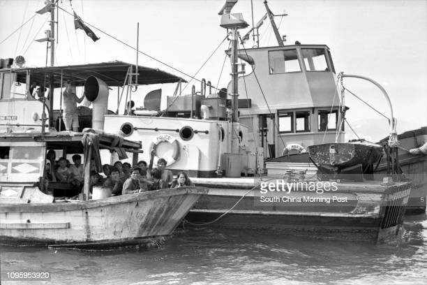 Vietnamese refugees awaiting immigration and health clearance sit in their boat moored next to a police launch off Stonecutters Island 01AUG77