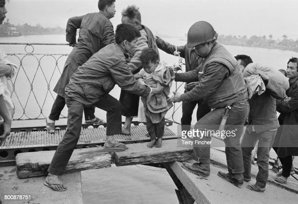 Vietnamese refugees crossing the wrecked Trung Tin Bridge over the Perfume River during the Battle of Hu Vietnam War February 1968