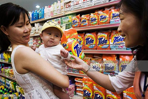 Vietnamese shopkeeper teases a baby boy while his mother picks up a box of Tide a Procter Gamble product at the Tax Trade Center in Ho Chi Minh City