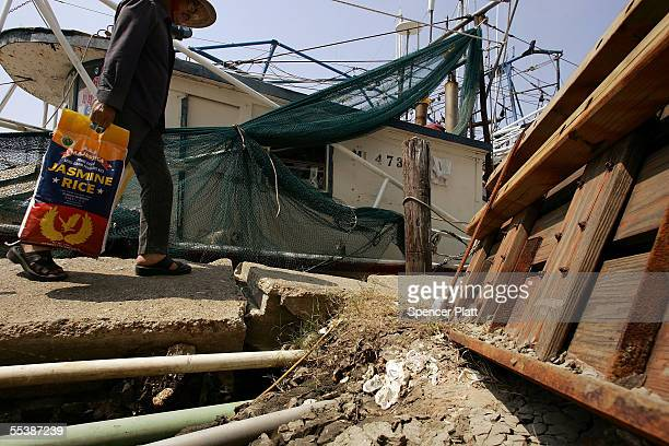 Vietnamese shrimp fisherman carries rice to his boat after his home was destroyed by Hurricane Katrina September 12 2005 in Biloxi Mississippi The...