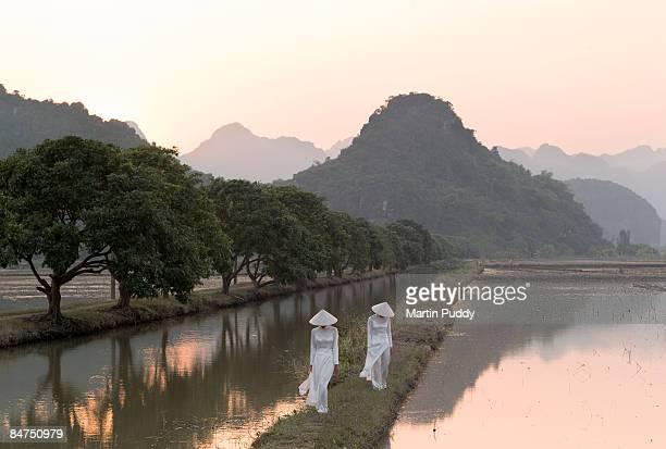 Vietnamese sisters walking along riverside