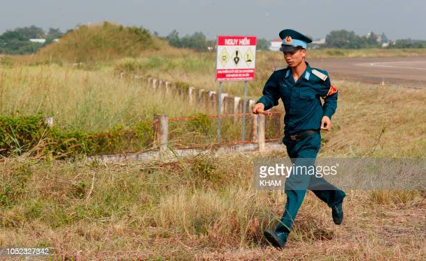 A Vietnamese soldier runs past the dioxin contaminated area as US Secretary of Defense Jim Mattis visits Bien Hoa airbase where the US army stored...