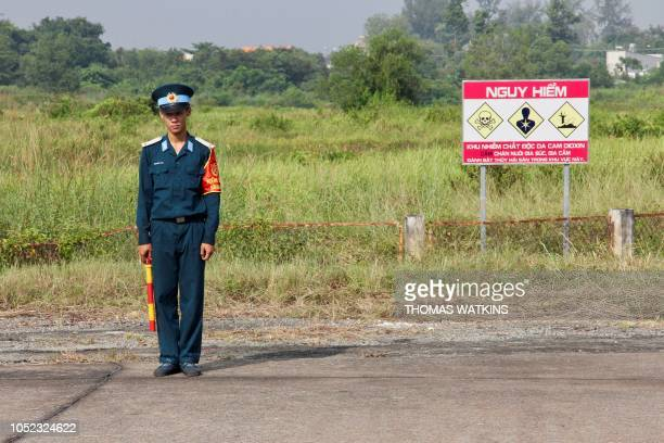 Vietnamese soldier stands next to a hazardous warning sign by a runway at Bien Hoa air base on the outskirts of Ho Chi Minh City as US Defence...