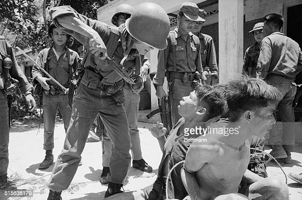 Vietnamese soldier threatens a Viet Cong prisoner with a knife in an effort to force him to reveal the whereabouts of his unit. Twenty Viet Cong were...