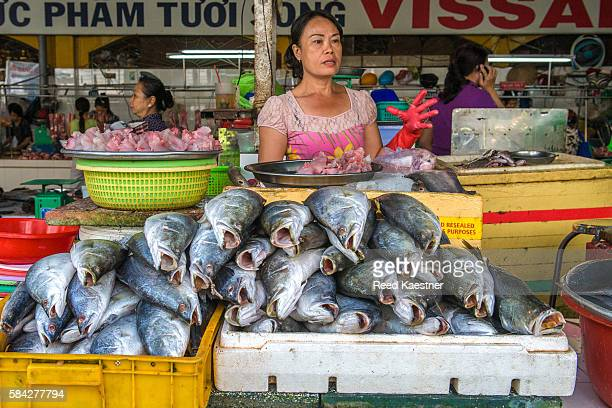 A vietnamese street vender sells seafood in market in Ho Chi Ming city