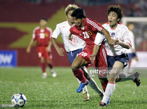 Vietnamese striker Thach Bao Khanh escapes South Korean Lee Chun Soo and Lee Min Sung during a World Cup 2006 qualyfying match between Vietnam and...