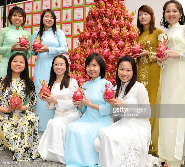 Vietnamese students in Japan pose with Vietnamese dragon fruit during a promotional event in Tokyo on December 16 2009 The Japanese government...