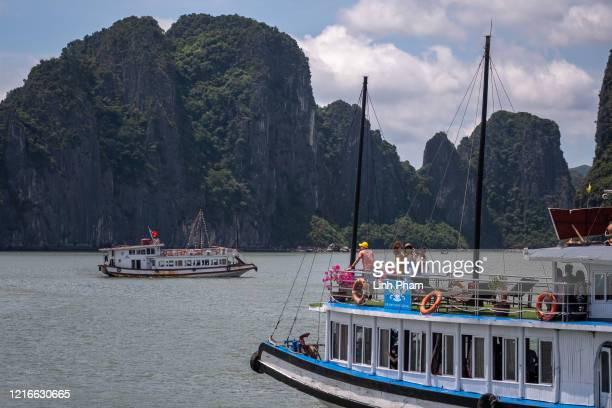 Vietnamese tourists pose for photographs on a boat touring Ha Long Bay after the Vietnamese government eased the lockdown following the coronavirus...