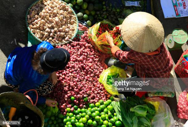 Vietnamese trader in a traditional hat selling agriculture product in the street market in