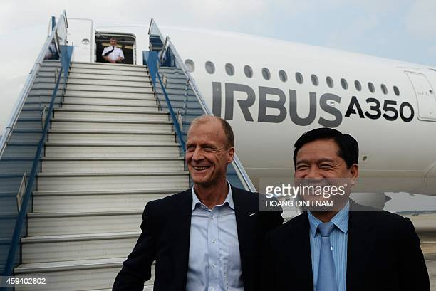 Vietnamese Transport Minister Dinh La Thang and CEO of Airbus Group Tom Enders pose for photographs before boarding an Airbus A350XWB for a demo...