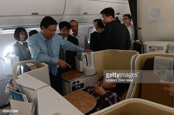 Vietnamese Transport Minister Dinh La Thang jokes with a boy lying on a business class lounge aboard an Airbus A350XWB during a demo flight from...