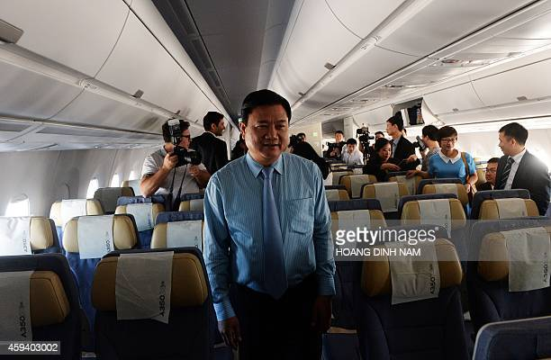 Vietnamese Transport Minister Dinh La Thang walks aboard an Airbus A350XWB during a demo flight from Hanoi's Noi Bai airport on November 22 2014 The...