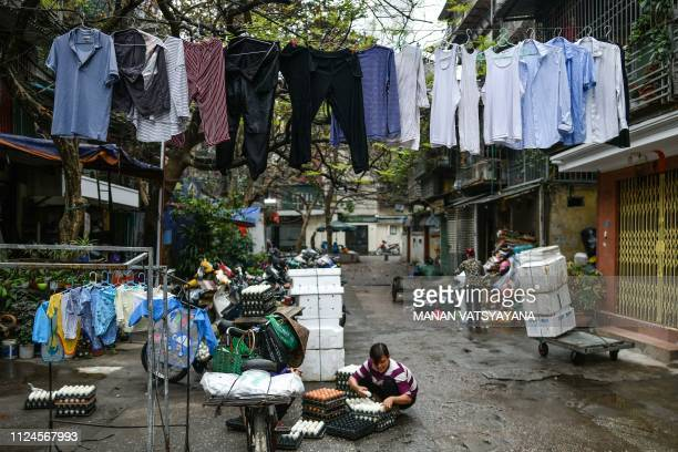 A Vietnamese vendor arranges a stack of eggs as clothes are hung out to dry at a backlane in Hanoi on February 13 2019