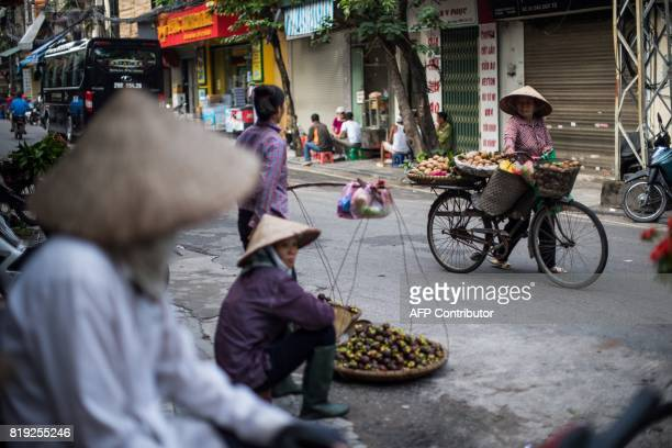 A Vietnamese vendor balances a load of vegetable as she walks in the streets of the old quarters of Hanoi on July 20 2017 / AFP PHOTO / Roberto...