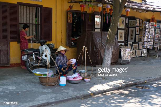 vietnamese vendor on the road in hoi an old town - poor service delivery stock pictures, royalty-free photos & images
